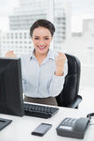 Excited businesswoman clenching fists at office desk Stock Photos