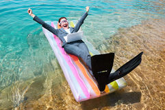 Excited businesswoman floating on lilo with laptop. Excited young Caucasian businesswoman wearing suit, flippers and swimming goggles floating with laptop on Royalty Free Stock Photo