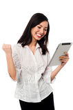 Excited businesswoman holding touch pad Stock Photo