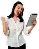 Excited businesswoman holding touch pad Stock Photography