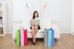 Excited businesswoman with laptop shopping online on sofa Stock Photos