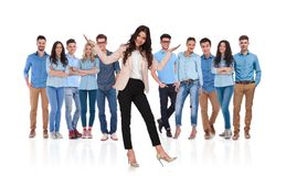 Excited businesswoman leader presenting her group standing behind her. Excited businesswoman team leader presenting her casual group standing behind her on white stock photography