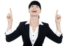 Excited businesswoman looking ad pointing upwards Stock Photo