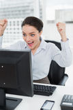 Excited businesswoman looks at the computer screen in office Stock Photos