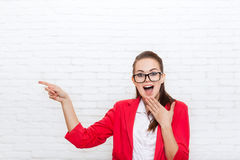 Excited businesswoman point finger to copy space wear red jacket glasses smile Stock Photo
