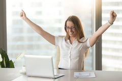 Excited businesswoman raising hands celebrating business success. Excited smiling businesswoman celebrating business success at workplace, raising hands looking Royalty Free Stock Photography