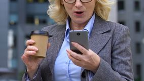 Excited businesswoman saying Wow to good app on cell phone while having coffee stock footage