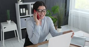 Excited businesswoman sharing online success through mobile phone. Excited businesswoman sharing good news on mobile phone received while working on office stock video footage