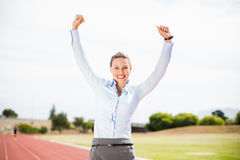 Excited businesswoman standing on the running track Royalty Free Stock Image
