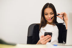 Excited businesswoman winning after achievement reading smart phone sitting in a desktop at office Royalty Free Stock Photo