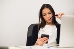 Excited businesswoman winning after achievement reading smart phone sitting in a desktop at office Royalty Free Stock Photos