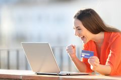 Excited buyer finding online offers on laptop royalty free stock image