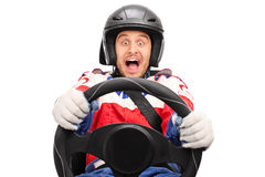 Excited car racer driving very fast. Fastened with seatbelt and looking at the camera isolated on white background Stock Images