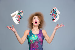 Excited carefree young woman amazed about flying shoes. Excited carefree surprised contnt joyful curly young woman amazed about flying shoes Royalty Free Stock Photography