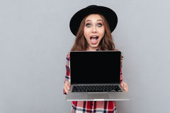Excited casual girl in plaid shirt holding blank screen laptop Royalty Free Stock Photos