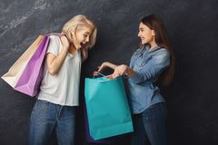 Excited casual girls with shopping bags. Happy casual girlfriends with shopping bags. Two excited shopaholics boasting with purchases at black sudio background Royalty Free Stock Image