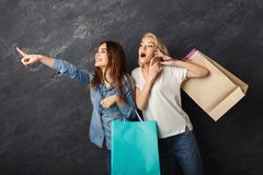 Excited casual girls with shopping bags. Happy casual girlfriends with shopping bags. Two excited shopaholics looking for sales and sharing info by smartphone at Royalty Free Stock Photography