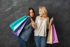 Excited casual girls with shopping bags. Happy casual girlfriends with shopping bags. Two excited shopaholics posing with purchases and using smartphone at black Stock Photography