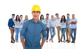 Excited casual group leader of engineers with his team behind. Excited casual group leader of engineers with his team standing behind on white background. He is royalty free stock photo