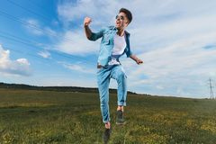 Excited casual man jumping outside on a field and celebrating stock image