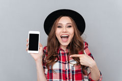 Excited casual woman pointing finger at blank screen mobile phone Royalty Free Stock Image
