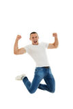 Excited Casual Young Caucasian Man Clenching His Fists and jumpi. Ng up in air, Isolated Over White Background Stock Photo