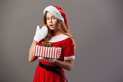 Excited charming mrs.Claus dressed in the red robe, Santa`s hat and white gloves holds the Christmas gift in her hands stock photo