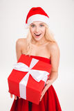 Excited cheerful blonde young woman holding red gift Stock Image