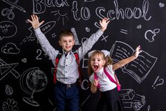 Excited and cheerful schoolkids standing before the chalkboard as a background with a backpack on their backs showing. Excited and cheerful schoolkids standing royalty free stock photo