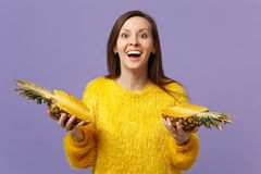 Excited cheerful young woman in fur sweater holding in hand halfs of fresh ripe pineapple fruit isolated on violet stock image