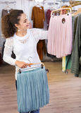 Excited  cheerful young woman shopping skirts Royalty Free Stock Photography
