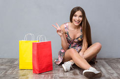 Excited cheerful young woman sitting on floor showing peace sign Stock Photography