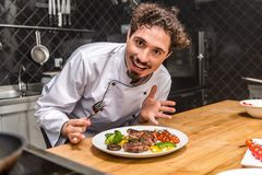 excited chef showing cooked vegetables with meat stock images