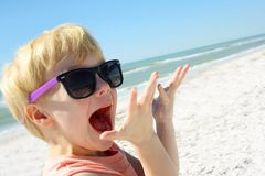Excited Child on Beach by Ocean. A young child is smiling and looking excited as he stands on the beach by the ocean Royalty Free Stock Images
