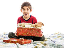 Excited child in bed with opened present Stock Photo