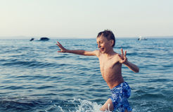 Excited child playing in sea laughing. Stock Images