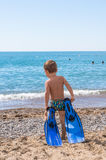 Excited child playing and surfing in sun protected swimsuit in ocean on vacations. White sand, Kid holding flippers for swimming. Adorable little blond kid boy Stock Photo