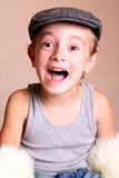 Excited Child wearing Flat Cap. A happy young boy child sitting wearing flat cap and tank shirt with big laugh Royalty Free Stock Photos