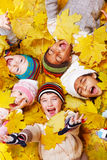 Excited children. In yellow leaves Royalty Free Stock Photography