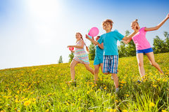 Excited children with balloons run in green field Stock Photo