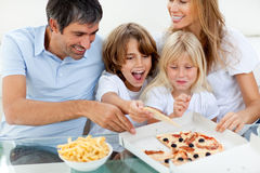 Excited children eating a pizza with their parents Royalty Free Stock Photography