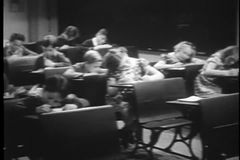 Excited children getting up from their desks in classroom stock video footage