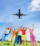 Excited children with hands up to plane in sky. Excited children with hands up to the flying plane in blue sky outdoors view from bottom Stock Photo