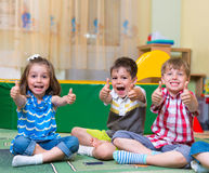 Excited children holding thumbs up. Group of excited children holding thumbs up Royalty Free Stock Image