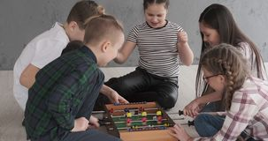 Excited children playing foosball at home. Excited boys and girls playing foosball together at home stock footage
