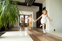 Excited children running into house, moving day in new home. Happy young family with cardboard boxes in new home at moving day concept, excited children running Royalty Free Stock Images