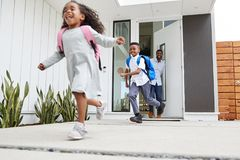 Excited Children Running Out Of Front Door On Way To School Watched By Father stock images