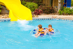Excited children in water park riding on slide with float. Funny excited children enjoying summer vacation in water park riding on slide with float. Little kids Royalty Free Stock Photography