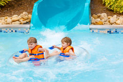 Excited children in water park riding on slide with float Stock Photos