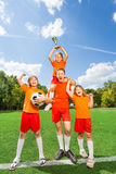 Excited children with won cup stand in pyramid Stock Photo